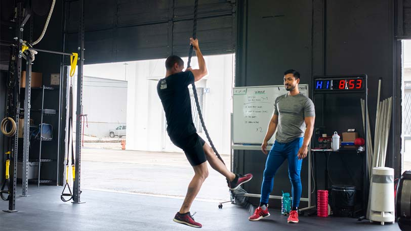 A man climbing rope in a gym